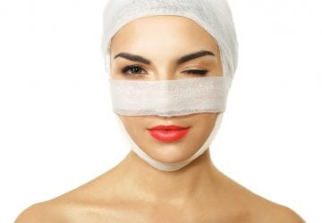 Young woman with a gauze bandage on her head and nose, isolated on white