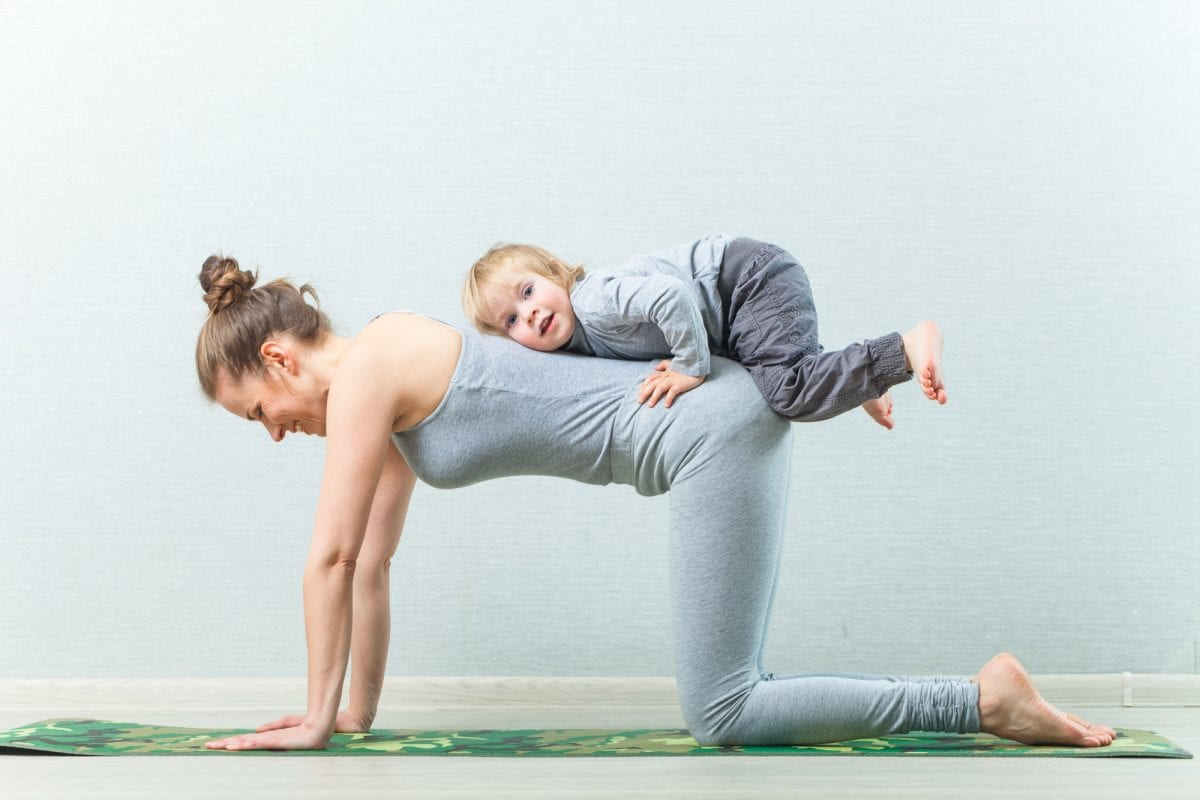 hatha yoga exercises mom with child practicing at home