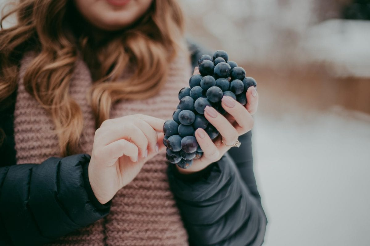 a woman outdoors eating grapes