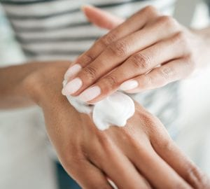a woman applying cream to her hands