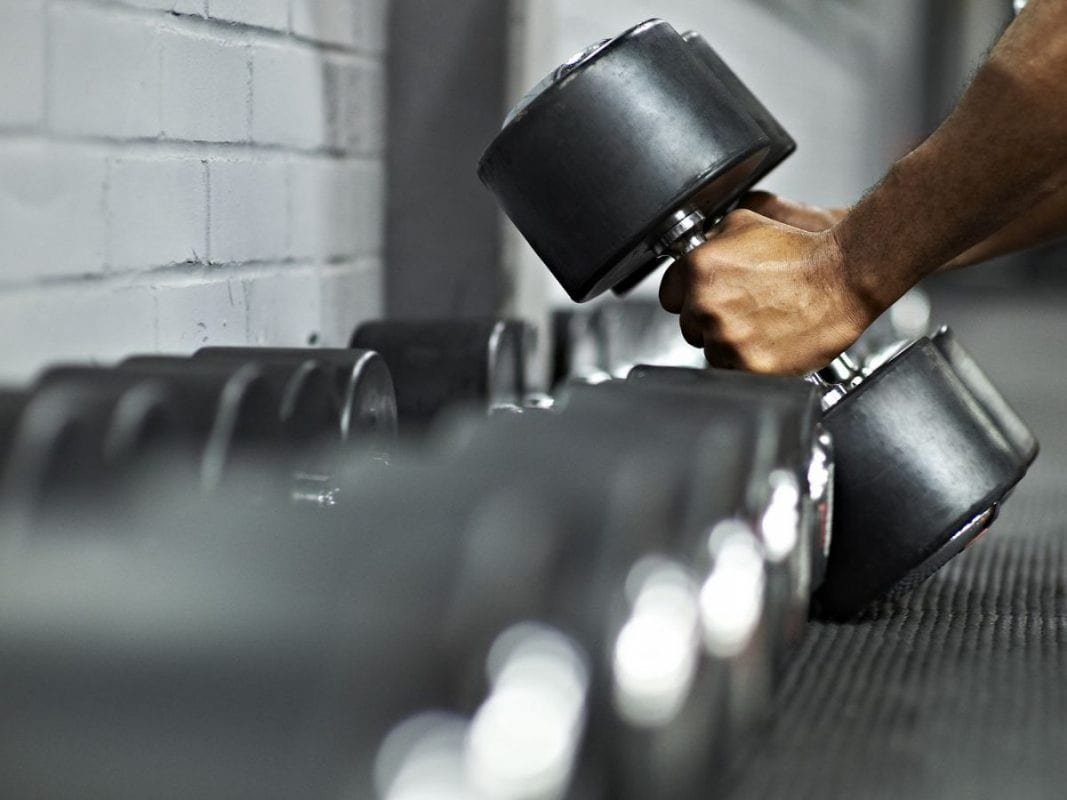 a man picking up a dumbell