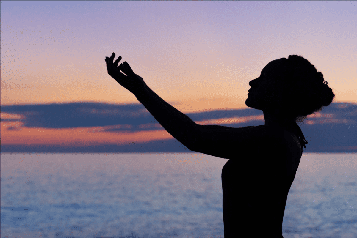 a woman meditating at the beach
