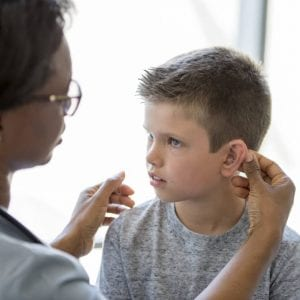 a young boy with a hearing aid