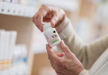 a woman holding a pill bottle