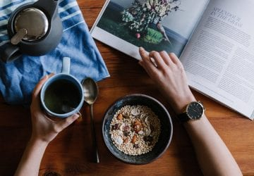 a woman eating breakfast and reading a magazine