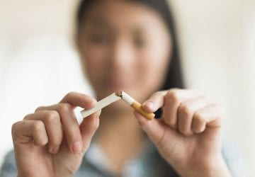 a woman breaking a cigarette