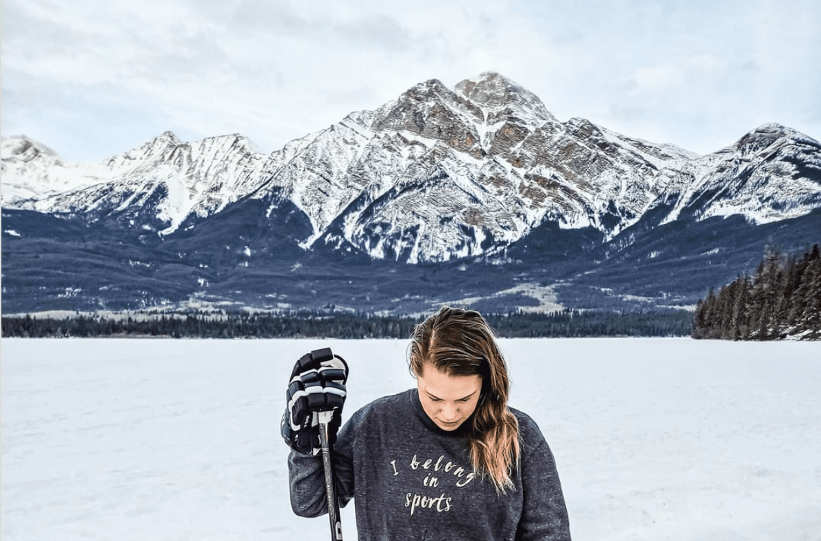 a woman playing hockey outdoors