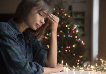 woman with headache near Christmas tree