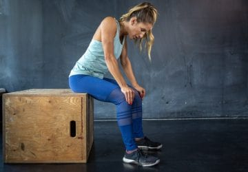 A woman sitting on a box recovering after a workout