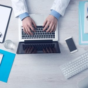 a doctor typing on their computer