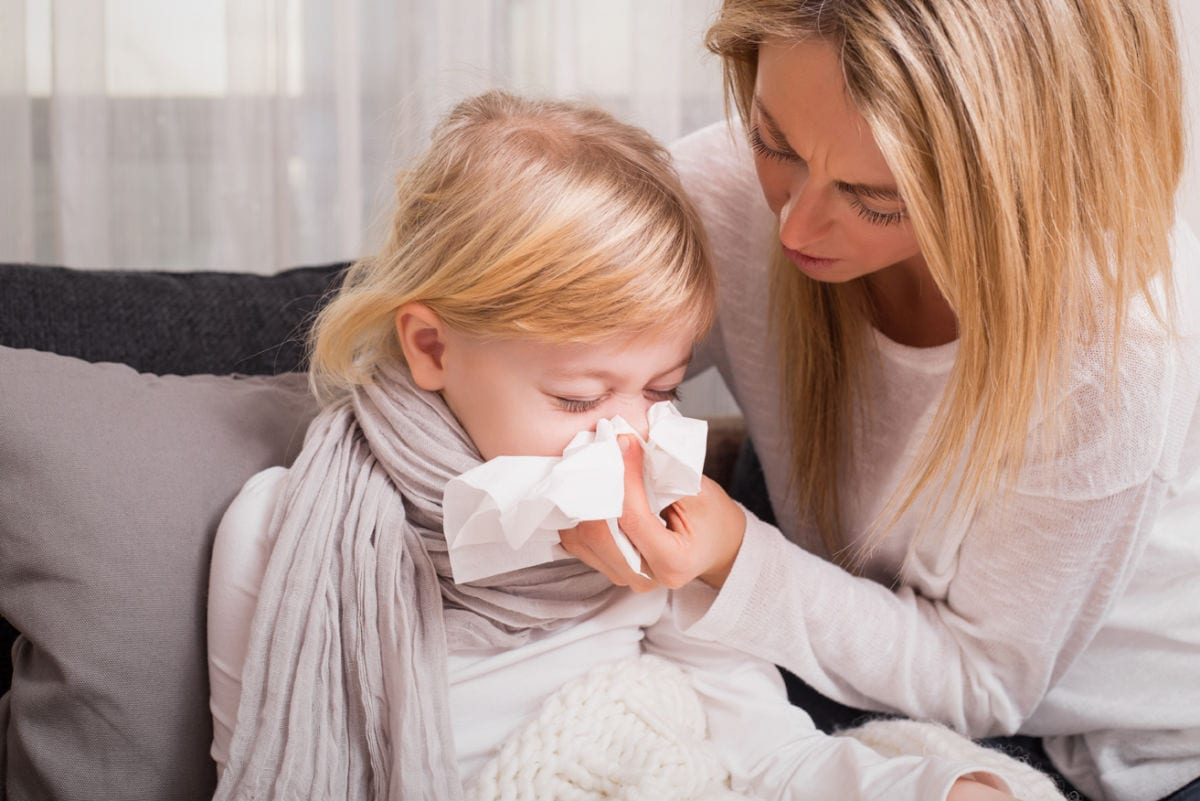 Little girl with cold and blowing her nose